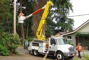 Man in a bucket truck servicing trees around power lines